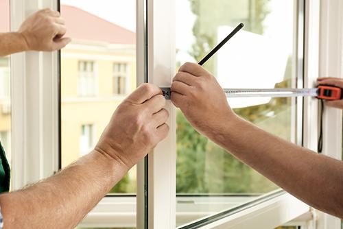 Zwei Fachmonteure  vermessen offenes Fenster